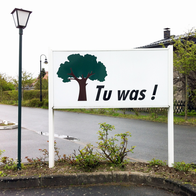 "Sign with picture of tree and text ""Tu was"""