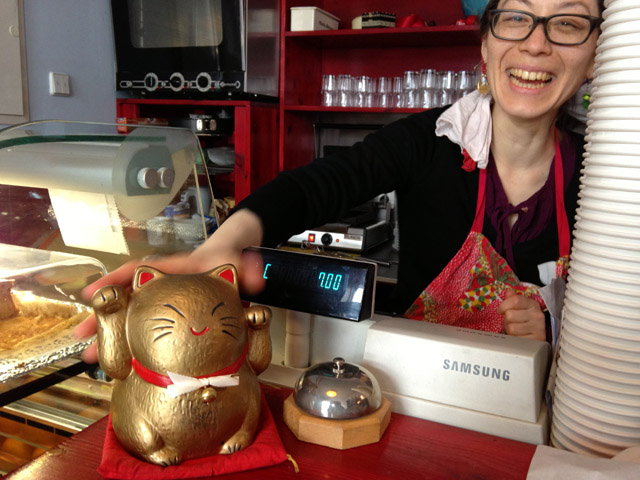 Yuki with lucky cat figurine at cash register