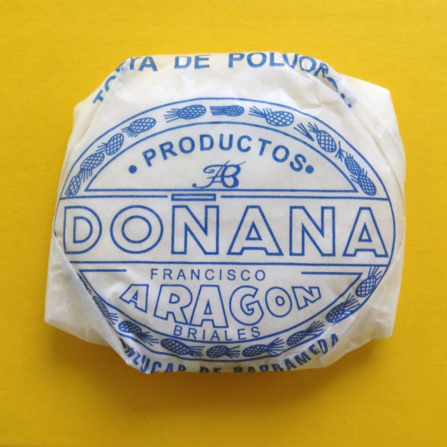 Cookie wrapped in white waxed paper with blue Spanish lettering