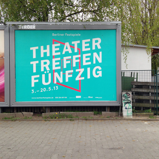 "Minimalist sky-blue billboard on a city street reading ""Theater Treffen Fünfzig"""