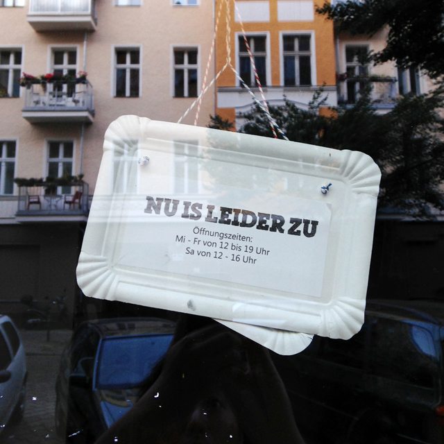 "Sign in window made of paper take-out tray reading ""Nu is leider zu"""
