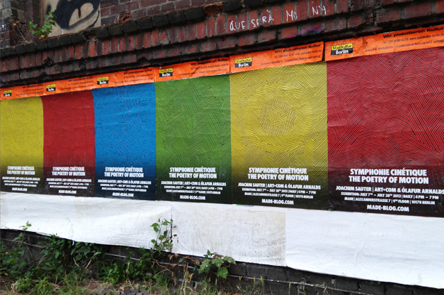 Row of four posters on a brick wall, in bright solid colors with geometric line graphics.