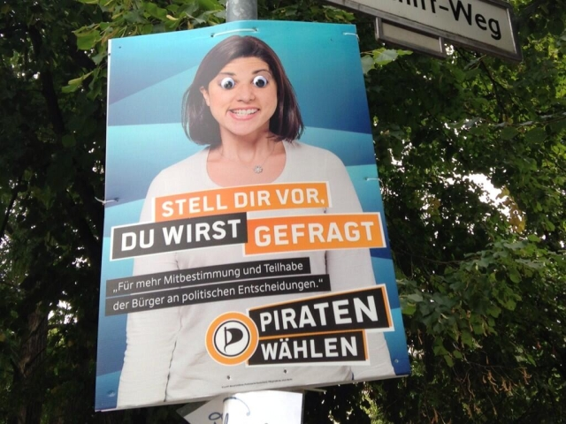 Campaign poster with photo of a woman, with googly eyes stuck on the poster over the eyes.