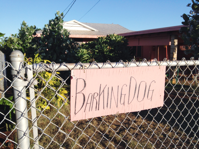 "Handpainted pink sign with ""Barking Dog"" on chain-link fence"