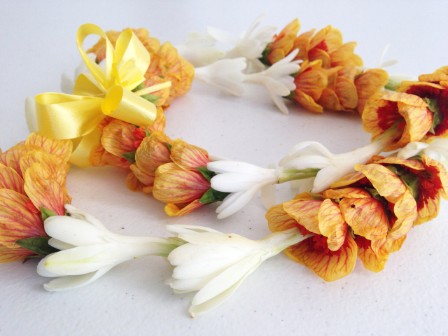 Closed (circular) lei of orange and white flowers with yellow bow.
