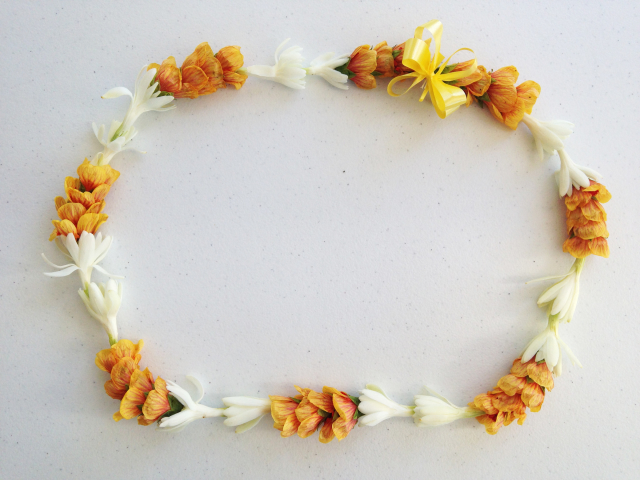 Closed (circular) lei of orange and white flowers.