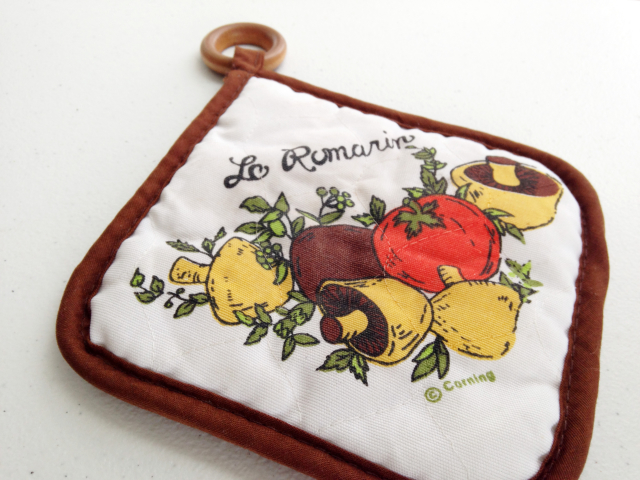 """Potholder from Corning with classic """"Le Romarin"""" vegetable pattern."""