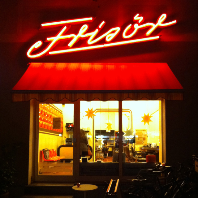 "Neon lettering ""Frisör"" above a salon window at night"