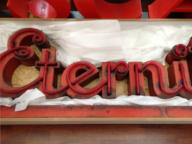 "Neon letters ""Eterni"" in a tissue-lined box"