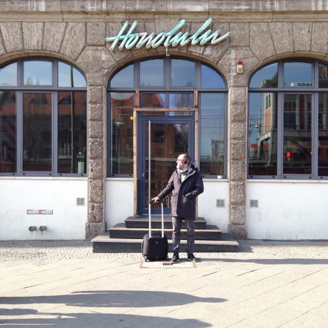 """Neon sign reading """"Honolulu"""" over doorway; man with suitcase standing in front of the door"""