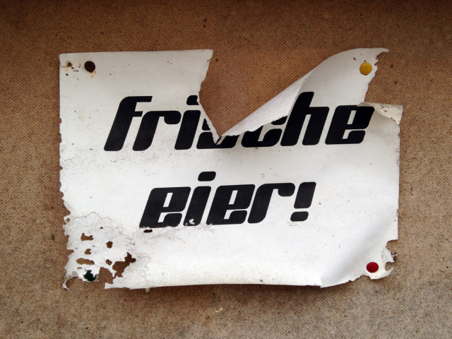 "Crumbling paper sign reading ""Frische eier!"" in a funky typeface"