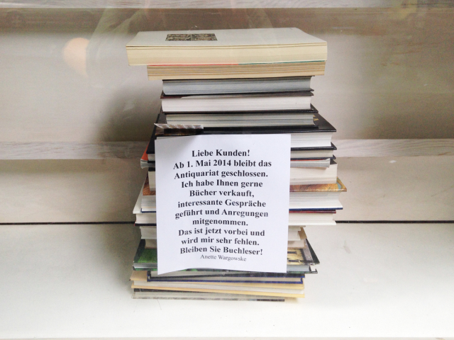 Sign on stack of books in a store window, announcing closing of store (in German)