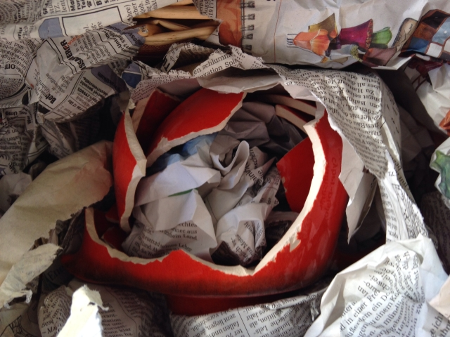 Pieces of a broken red teapot in newspaper