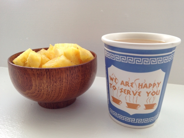 Wooden bowl of pineapple and a ceramic cup of coffee made to look like a typical New York Greek deli paper cup