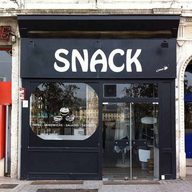 "Small shop with large sign reading ""SNACK"""