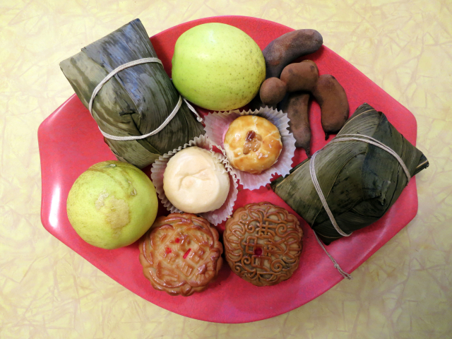 Tray with mooncakes, sticky rice dumplings wrapped in leaves, other Chinese cakes, lemons and tamarind pods